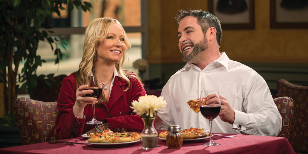 smiling couple dining drinking glasses of wine