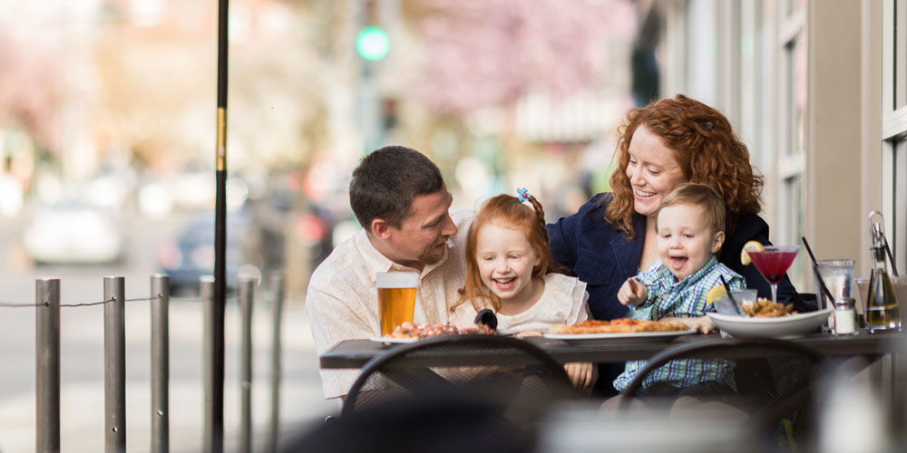 family smiling at a table over food